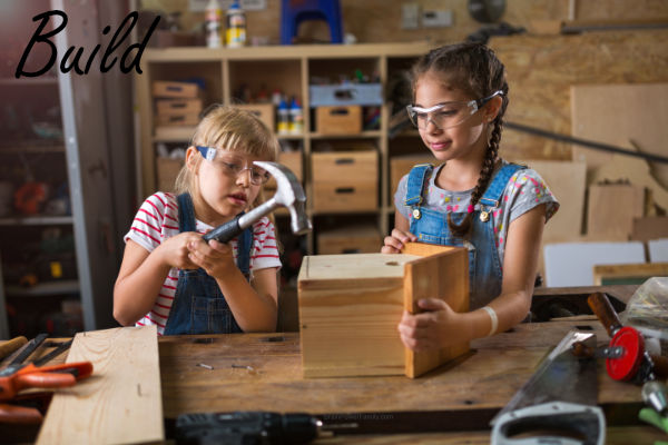 Two girls building a birdhouse together as a family activity