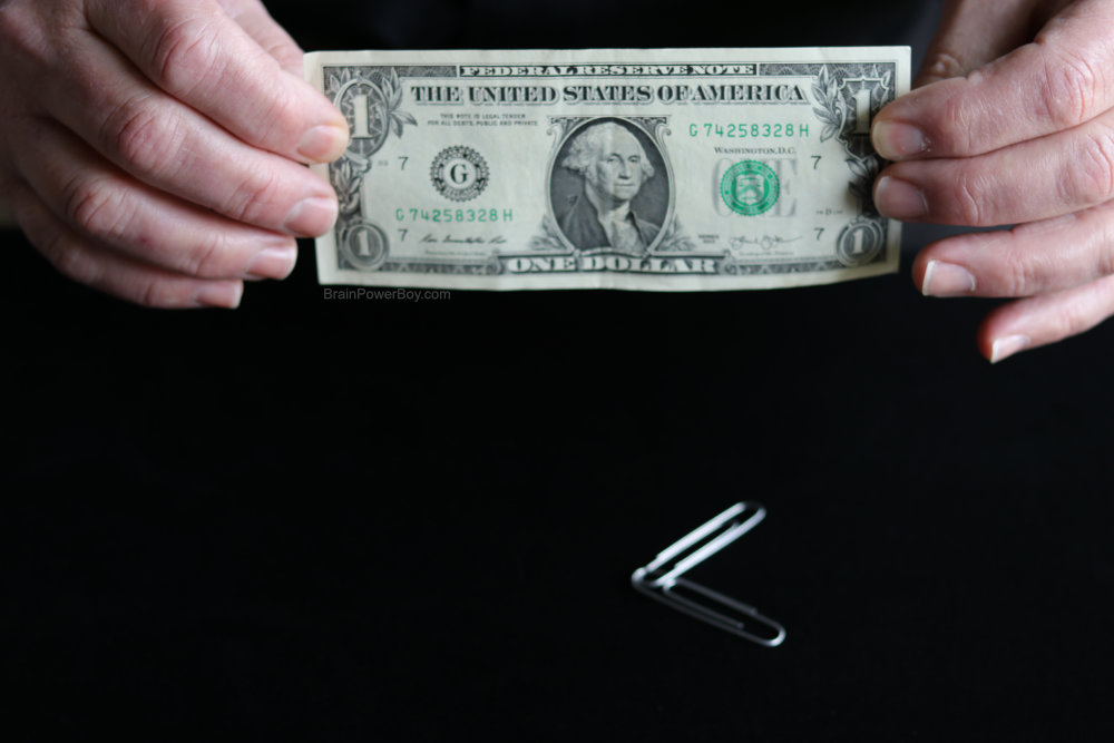 dollar bill in hands with two connected paperclips