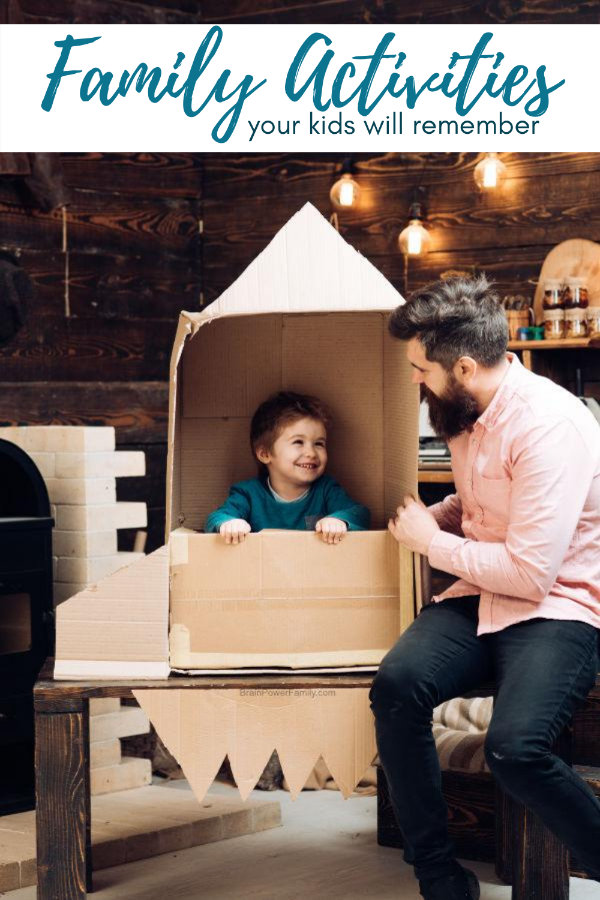 What to do with kids indoors at home. Dad builds cardboard rocket for child.