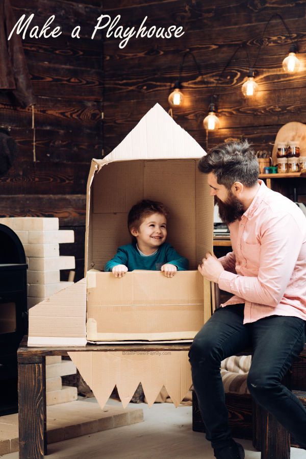 Dad making a cardboard playhouse rocket for child